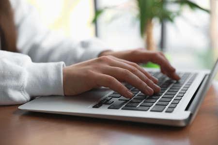 Persona joven que trabaja con el portátil en la cafetería, primer plano