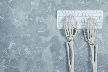 Human skeleton using computer keyboard at grey marble table, top view. Space for text