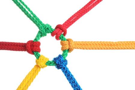Cuerdas de colores atados juntos aislados en blanco. Concepto de unidad Foto de archivo