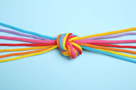 Colorful ropes tied together on light blue background, top view. Unity concept Banque d'images