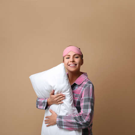 Beautiful woman with pillow on beige background. Bedtime Stock fotó