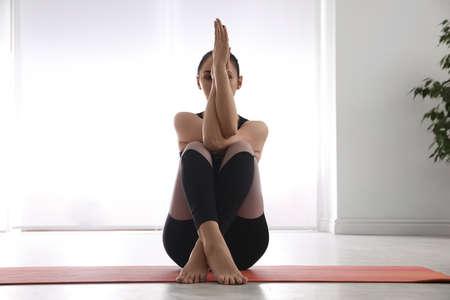 Woman practicing eagle asana in yoga studio. Garudasana pose Stockfoto