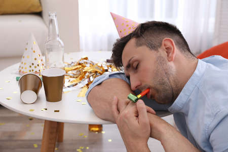 Young man in festive cap sleeping at table in room after party Stok Fotoğraf - 137879525
