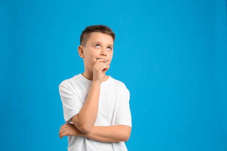 Portrait of preteen boy on light blue background, space for text