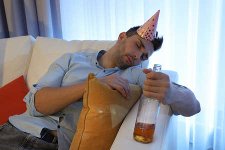 Young man with festive cap sleeping on sofa in room after party Stok Fotoğraf - 137880001