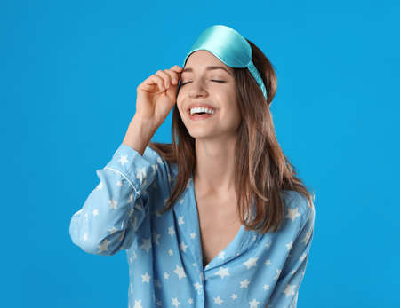 Beautiful woman wearing pajamas and sleep mask on light blue background. Bedtime Stok Fotoğraf - 137880078