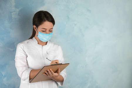 Arts met wegwerpmasker op gezicht met klembord tegen lichtblauwe achtergrond. Ruimte voor tekst Stockfoto