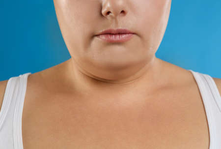 Woman with double chin on blue background, closeup