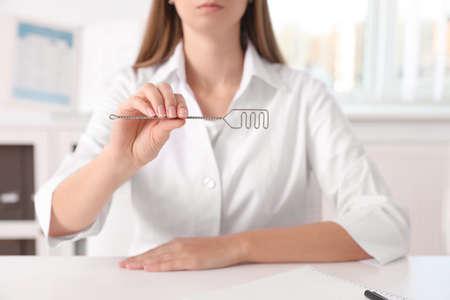 Speech therapist with logopedic probe in clinic, closeup