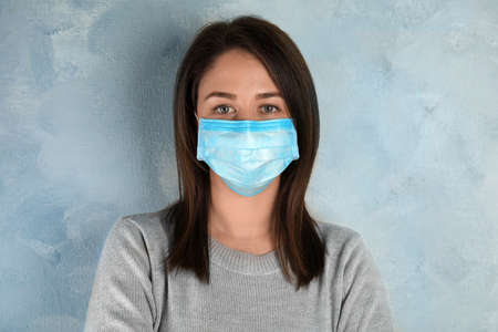 Femme avec masque jetable sur le visage sur fond bleu clair