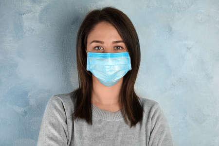 Mujer con máscara desechable en la cara contra el fondo azul claro