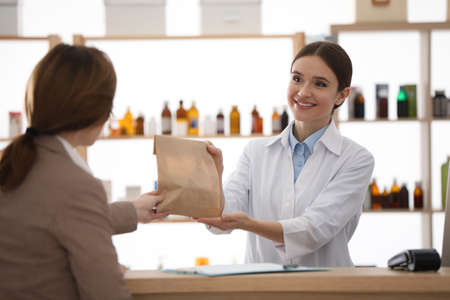 Pharmacist giving medicine to customer in drugstore