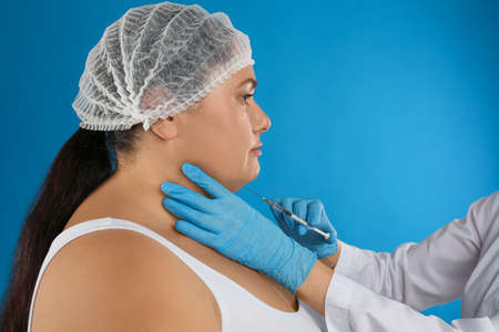 Woman with double chin getting injection on blue background. Cosmetic surgery Stock Photo
