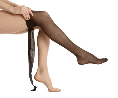 Woman putting on tights on white background, closeup