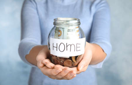 Woman holding glass jar with money and tag HOME on light blue background, closeup