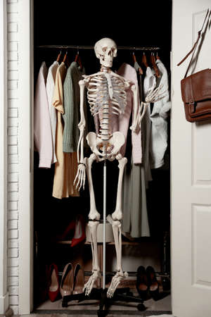Artificial human skeleton model among clothes in wardrobe room 写真素材