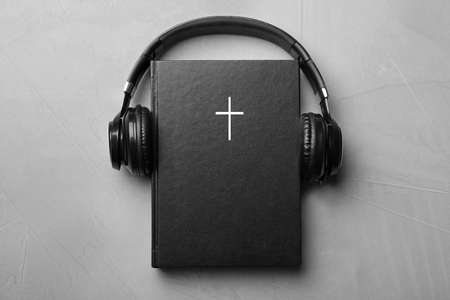 Bible and headphones on light grey background, top view. Religious audiobook