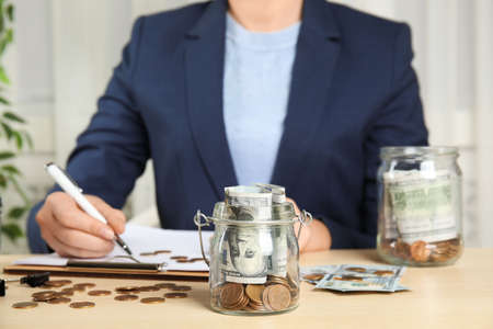 Woman with glass jar of money at wooden table, closeup
