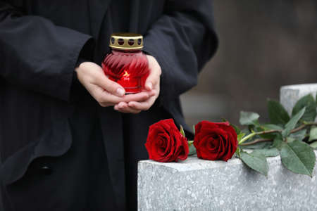 Woman holding candle near light grey tombstone with red roses outdoors, closeup. Funeral ceremony 스톡 콘텐츠