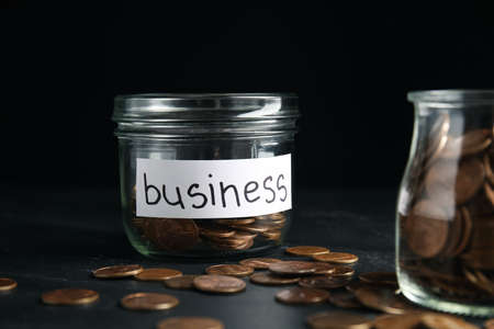Glass jar with coins and tag BUSINESS on black table