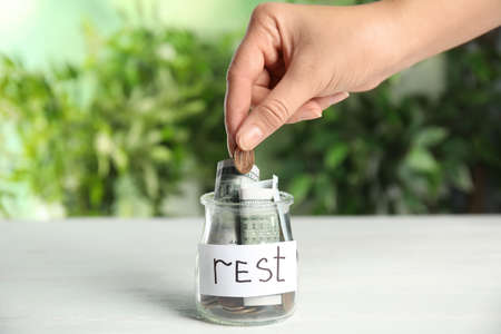 Woman putting coin into jar with tag REST on white wooden table, closeup
