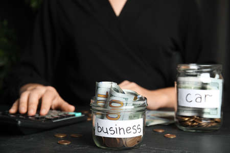 Woman using calculator near glass jar with money and tag BUSINESS on black table, closeup