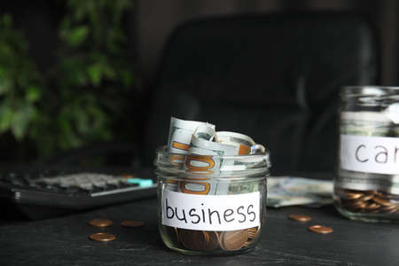 Glass jar with money and tag BUSINESS on black table