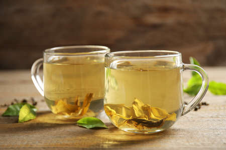 Cups of green tea and leaves on wooden table