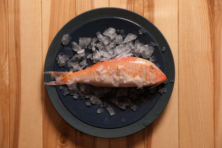 Fresh raw fish with ice on wooden table, top view Standard-Bild