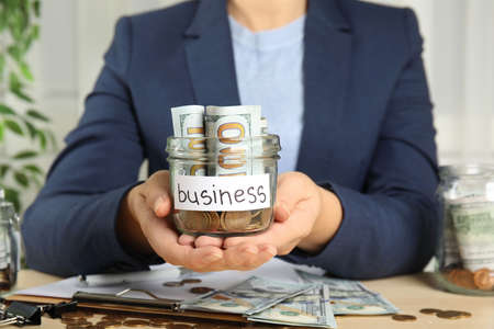 Woman holding glass jar with money and tag BUSINESS at wooden table, closeup
