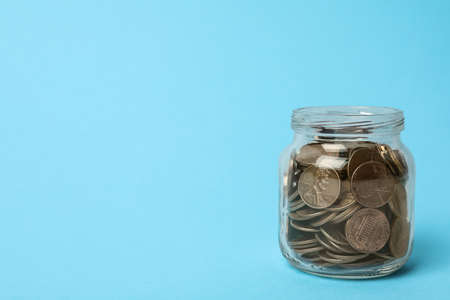 Glass jar with coins on light blue background, space for text