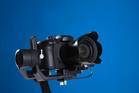 Modern professional video camera on blue background