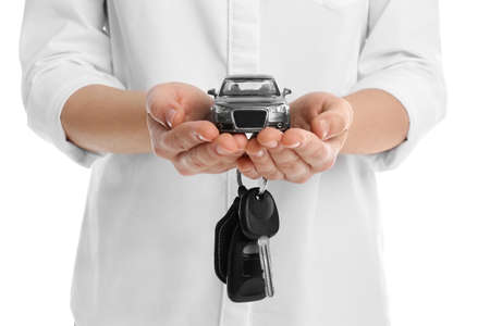 Woman holding key and miniature automobile model on white background, closeup. Car buying Reklamní fotografie