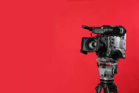 Modern professional video camera on red background. Space for text