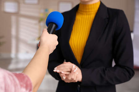 Professional journalist interviewing young woman in room, closeup