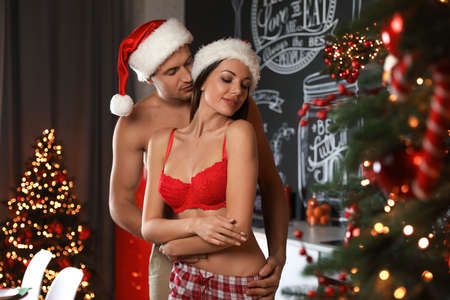 Passionate young couple enjoying each other at home. Christmas celebration