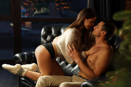 Passionate couple enjoying each other on sofa at home. Christmas celebration