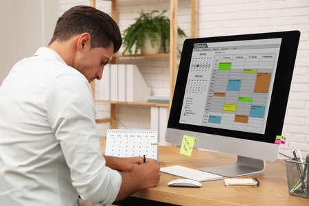 Man using calendar app on computer in office Stock Photo - 138183744