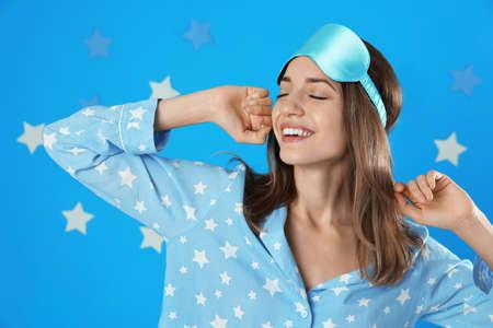 Beautiful woman wearing pajamas and sleep mask on light blue background. Bedtime Stok Fotoğraf - 137882221