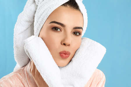 Young woman wiping face with towel on light blue background