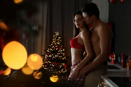 Passionate young couple enjoying each other in kitchen. Christmas celebration