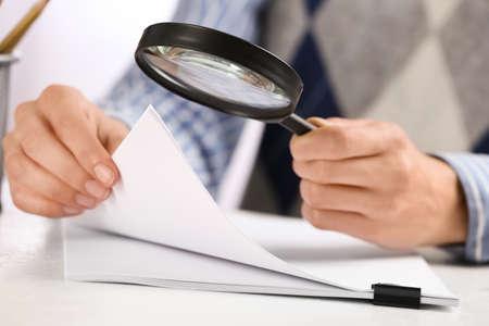 Woman using magnifying glass at table, closeup