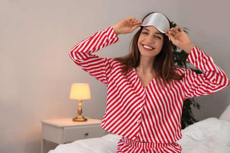 Beautiful woman wearing pajamas and sleep mask indoors. Bedtime