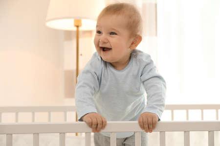 Cute little baby in crib at home Archivio Fotografico