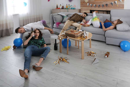 Drunk friends suffering from hangover in messy room after party Stok Fotoğraf - 137882583