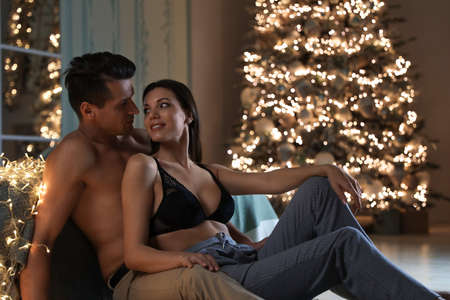Passionate young couple enjoying each other in room decorated for Christmas