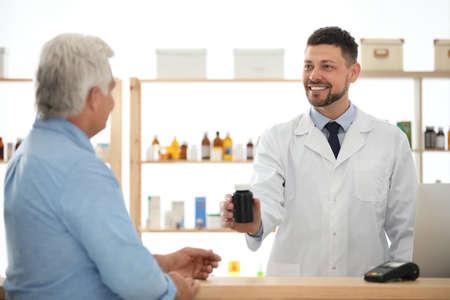 Pharmacist giving medicine to customer in drugstore