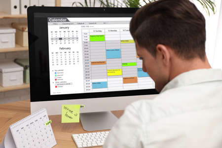 Man using calendar app on computer in office