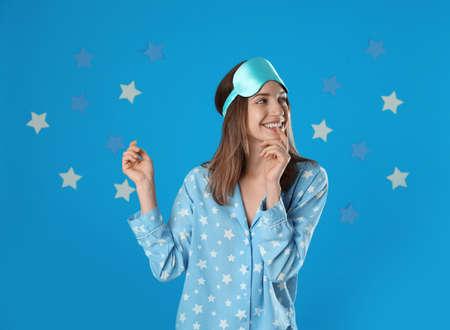 Beautiful woman wearing pajamas and sleep mask on light blue background. Bedtime Stock fotó