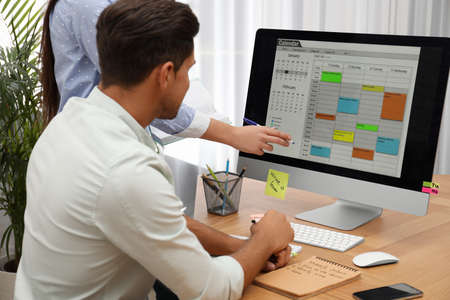 Colleagues working with calendar app on computer in office